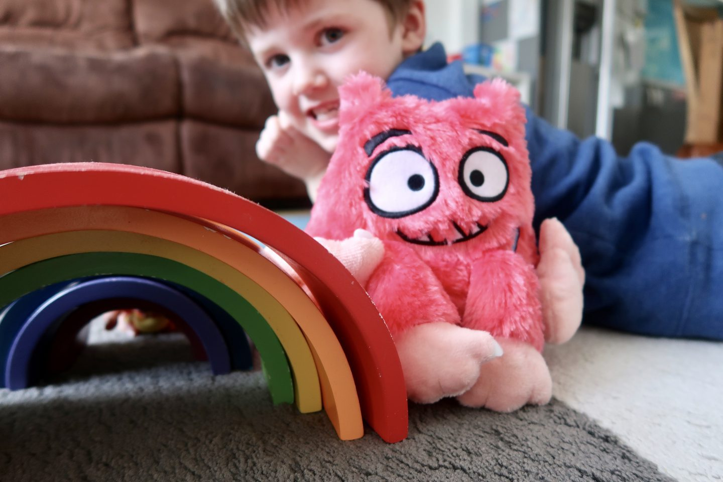 A wooden rainbow next to a fluffy monster toy. There is a boy smiling in the background slightly out of focus
