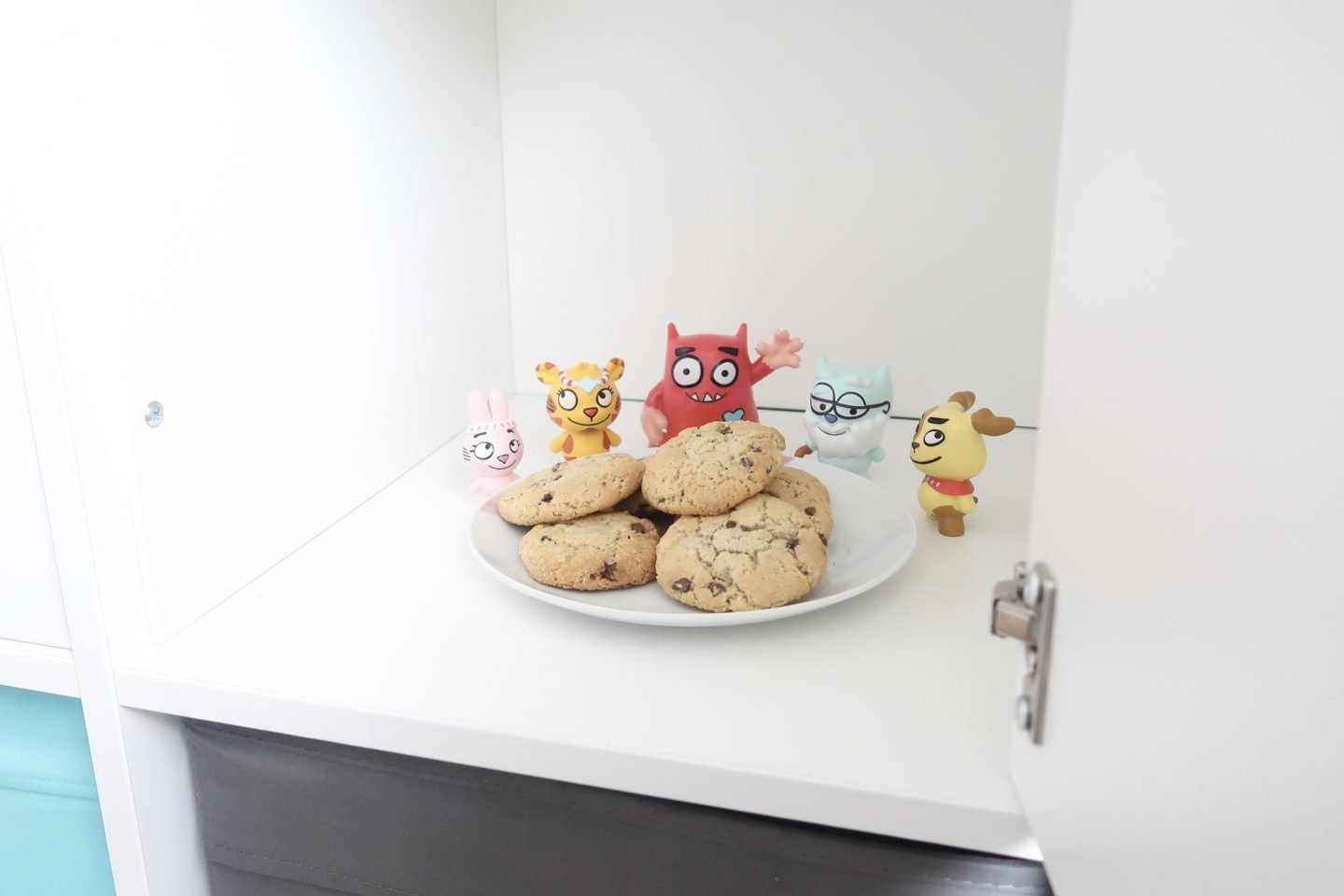 A plate of cookies surrounded by Love Monster figurines