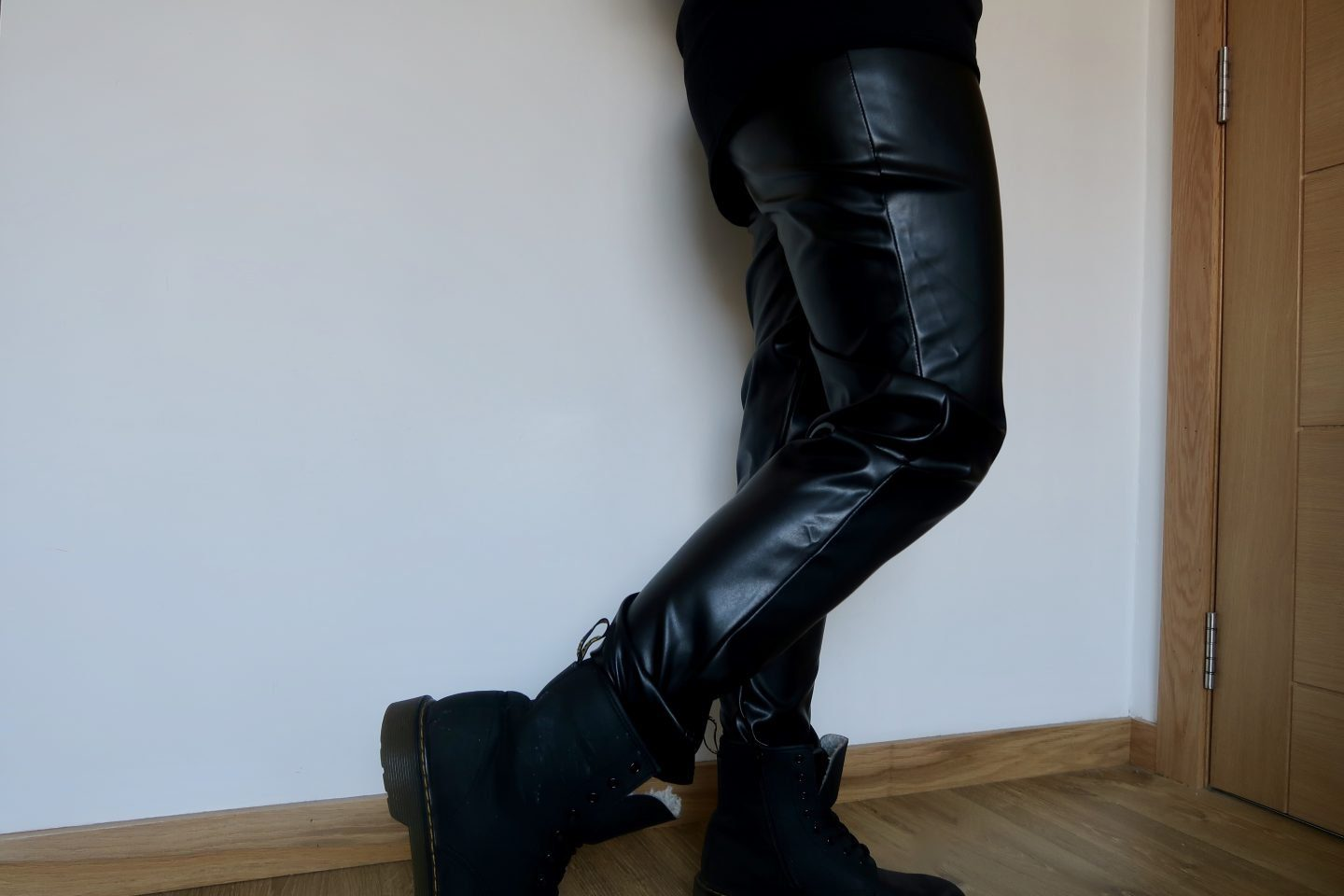A pair of legs wearing black fake leather trousers
