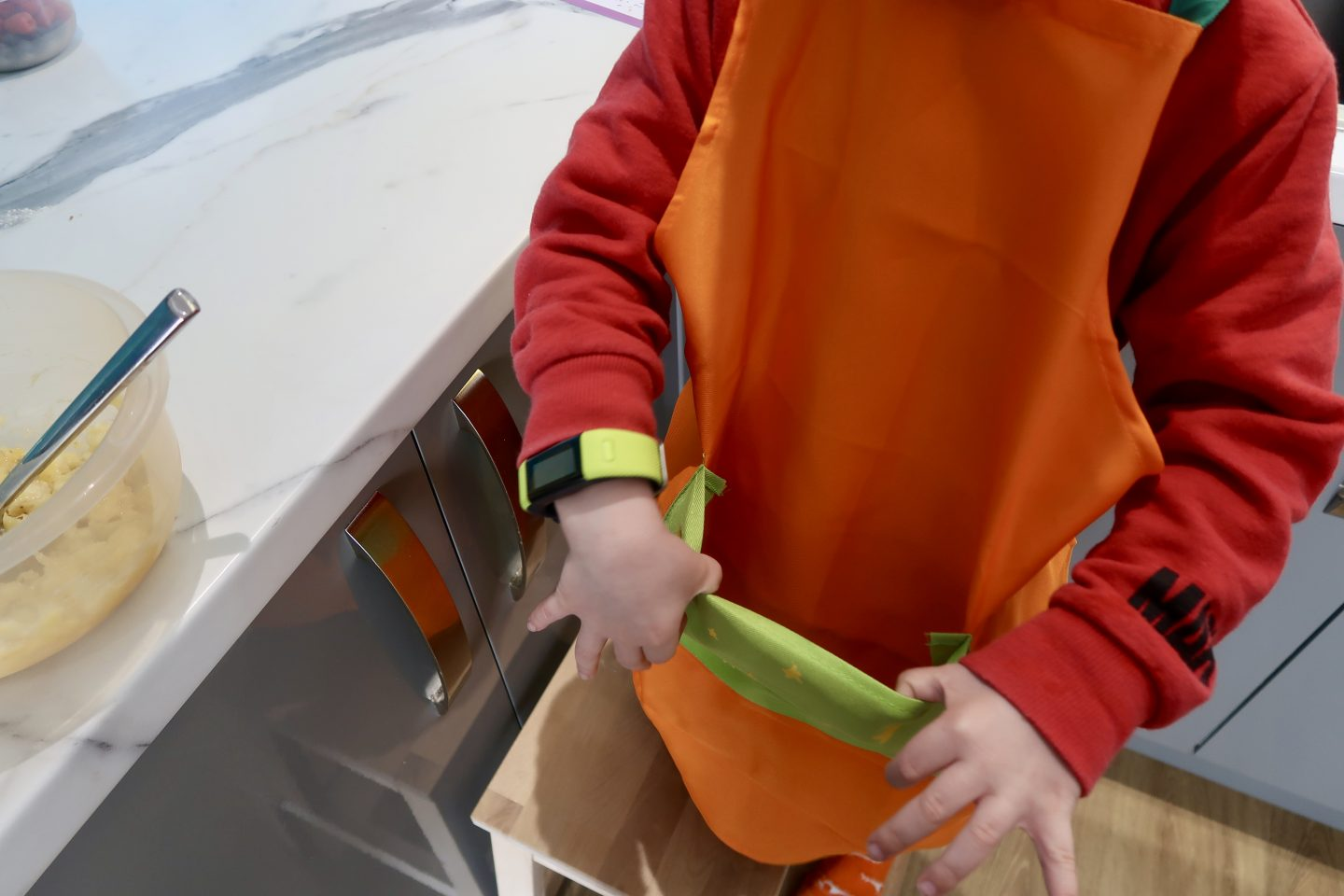 A child wearing and apron and pulling out the apron pocket
