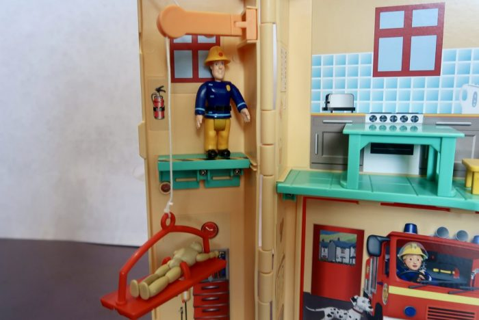 Fireman Sam figure standing on a ledge next to a pulled with a red stretcher and training dummy on it