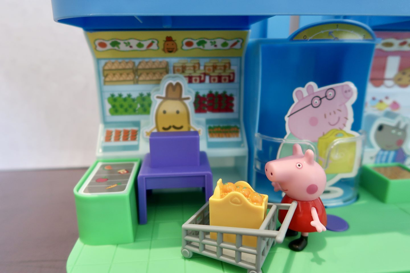 A Peppa Pig figure with a shopping trolley in a toy shop