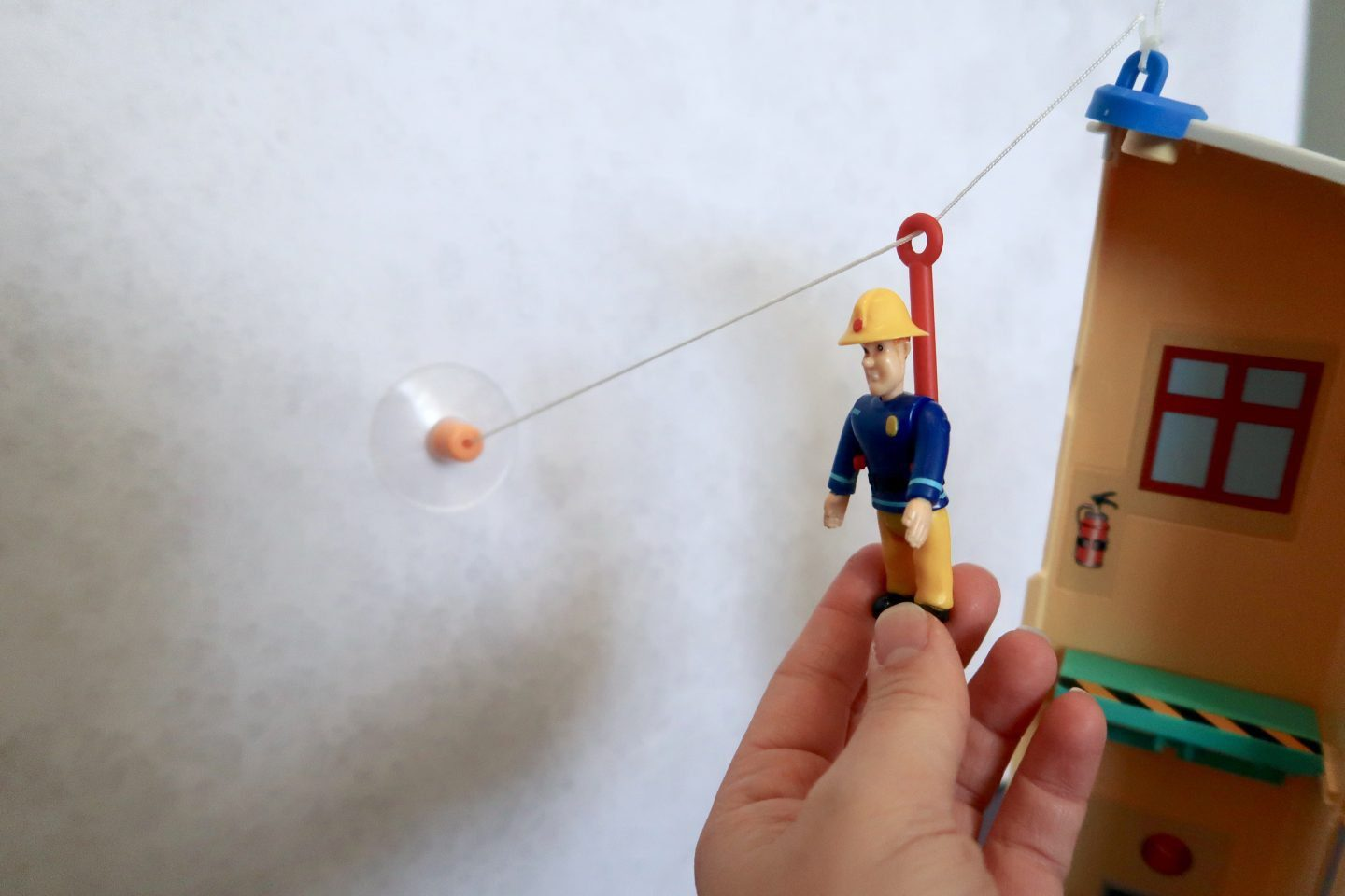 A Fireman Sam toy going down a zip wire