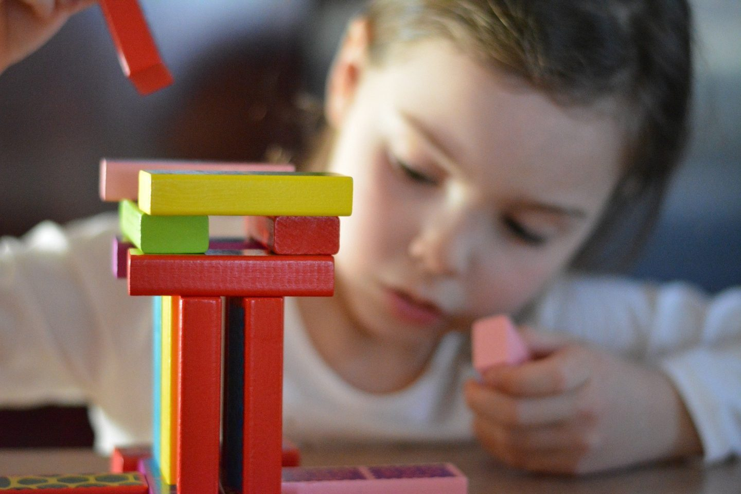 A girl making a tower with multicoloured wooden blocks