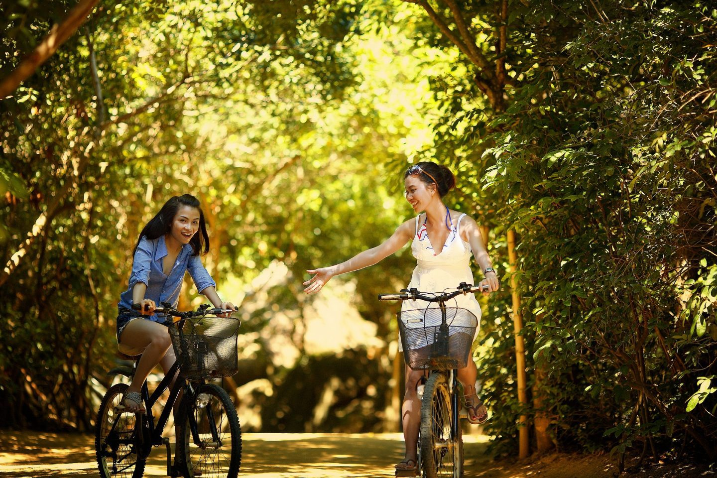 2 girls riding bicycles through the woods. The girl on the right is reaching towards the girl on the left