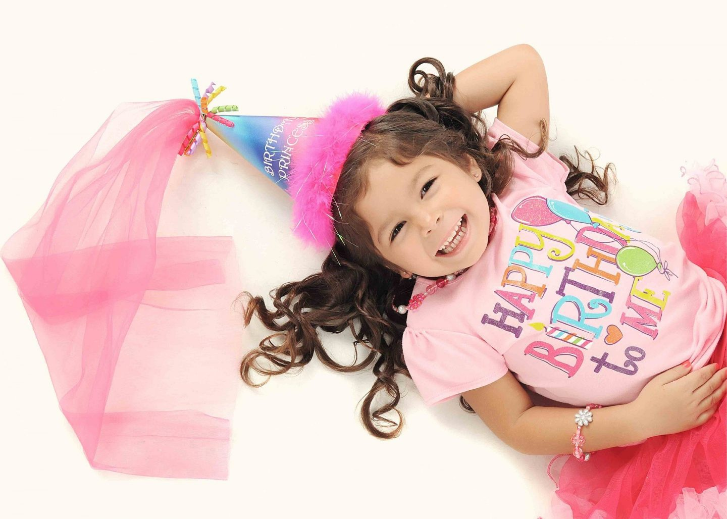 """A little girl dressed in pink with a """"Happy Birthday"""" t-shirt on and a crown"""