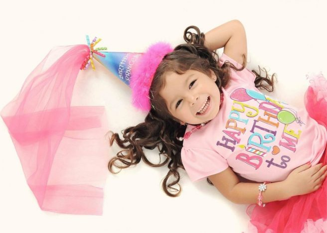 "A little girl dressed in pink with a ""Happy Birthday"" t-shirt on and a crown"