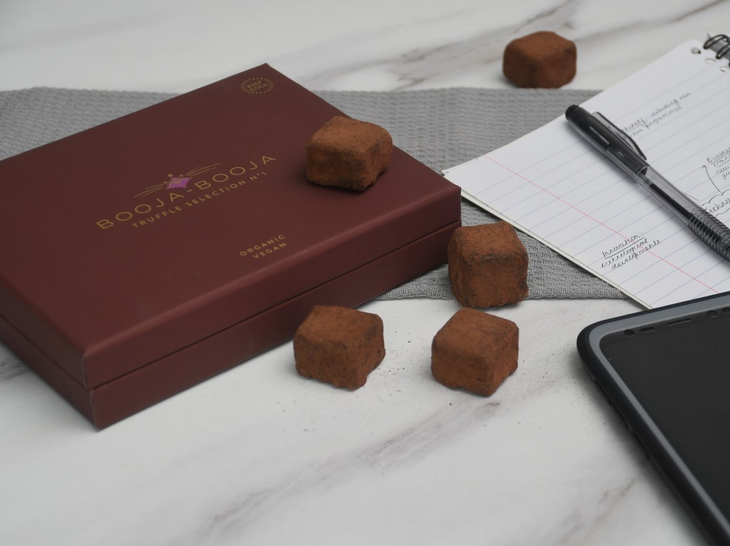 A box of chocolates on a counter next to a pen and paper. There are chocolate truffles scattered around