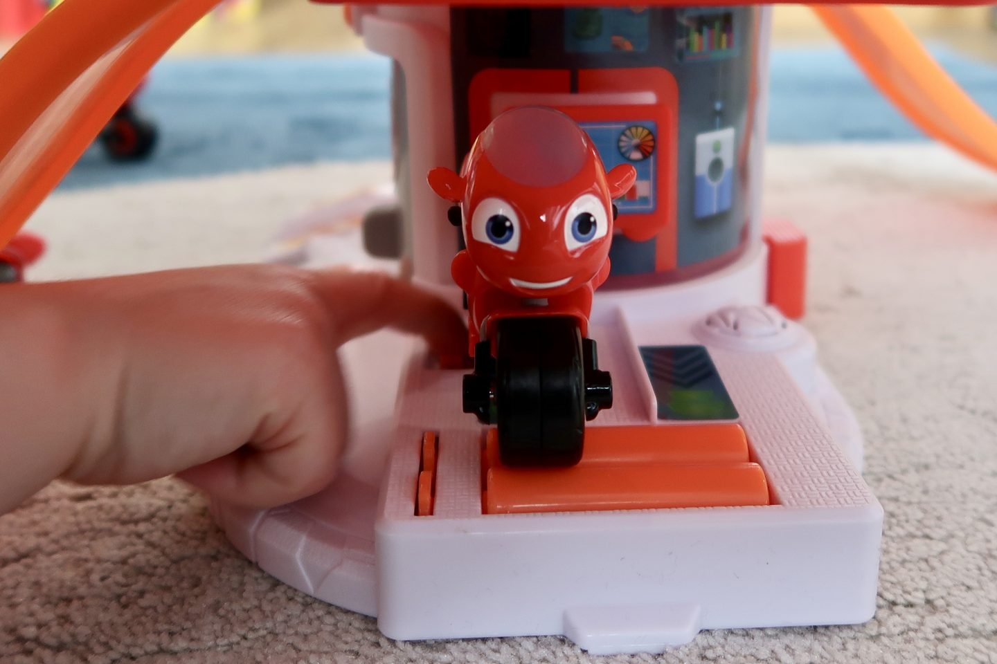 A Ricky Zoom toy on the tyre checker of Ricky's House Play set. The toy is facing the camera while a child's hand turns the spinners