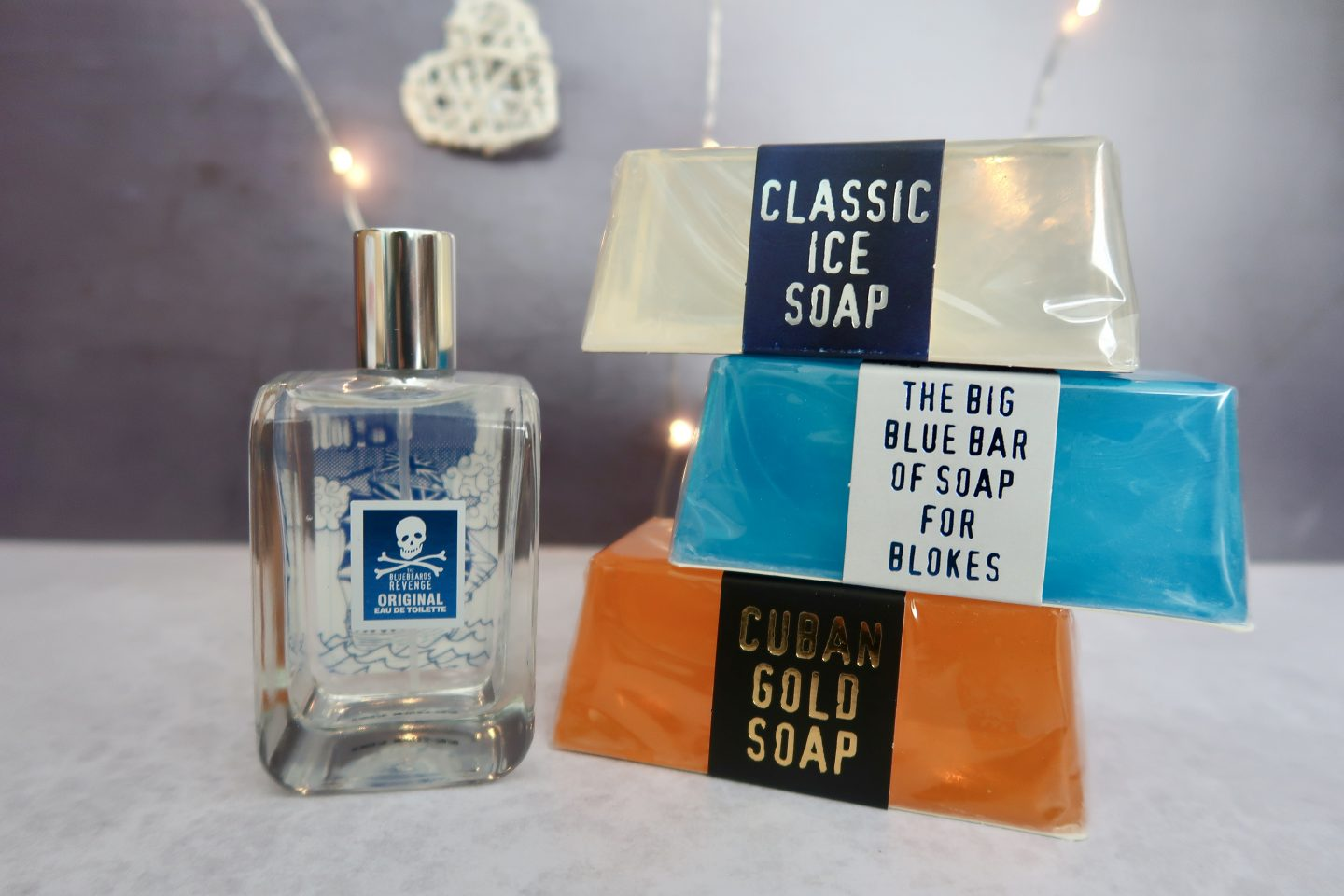 A bottle of aftershave next to a stack of 3 bars of soaps in ingot shape