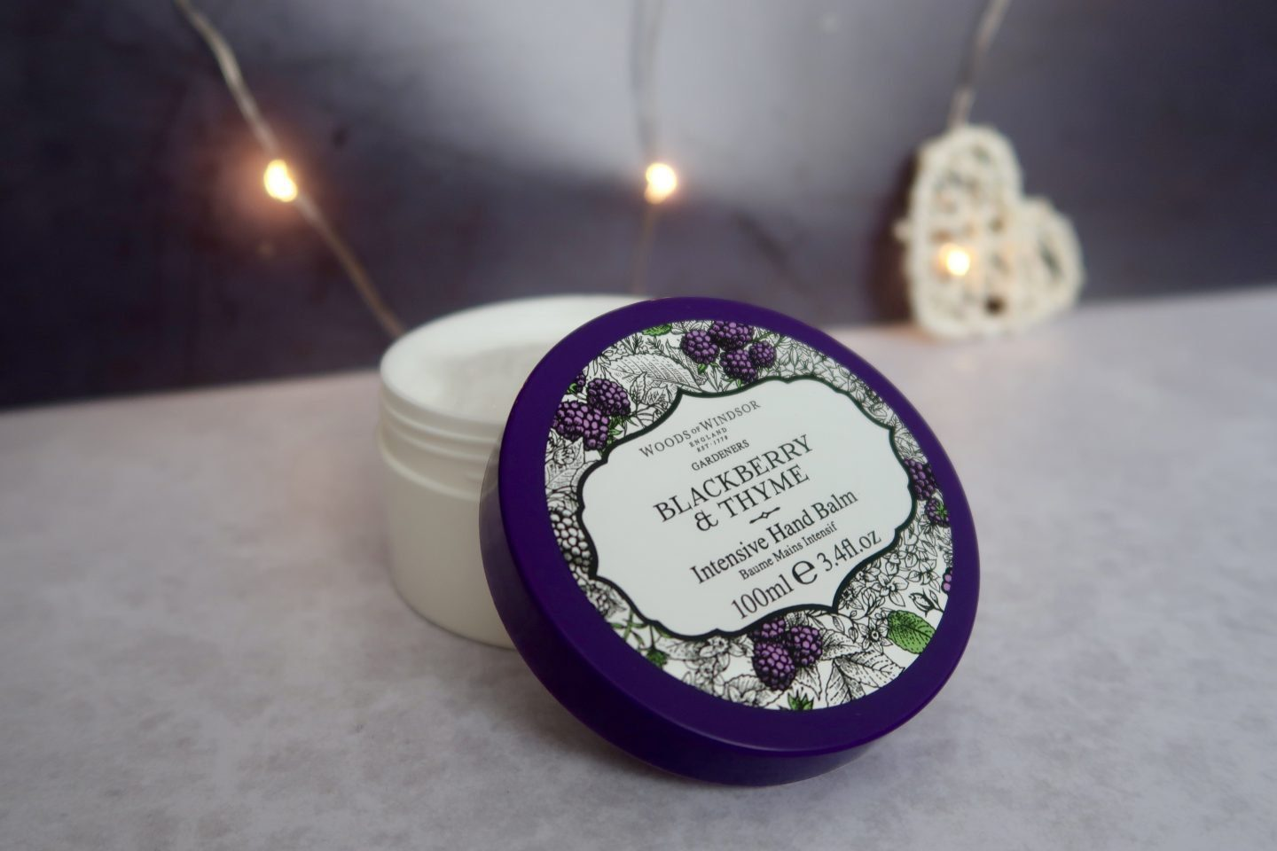 A tub of intense hand balm sitting open with the lid propped up on the tub
