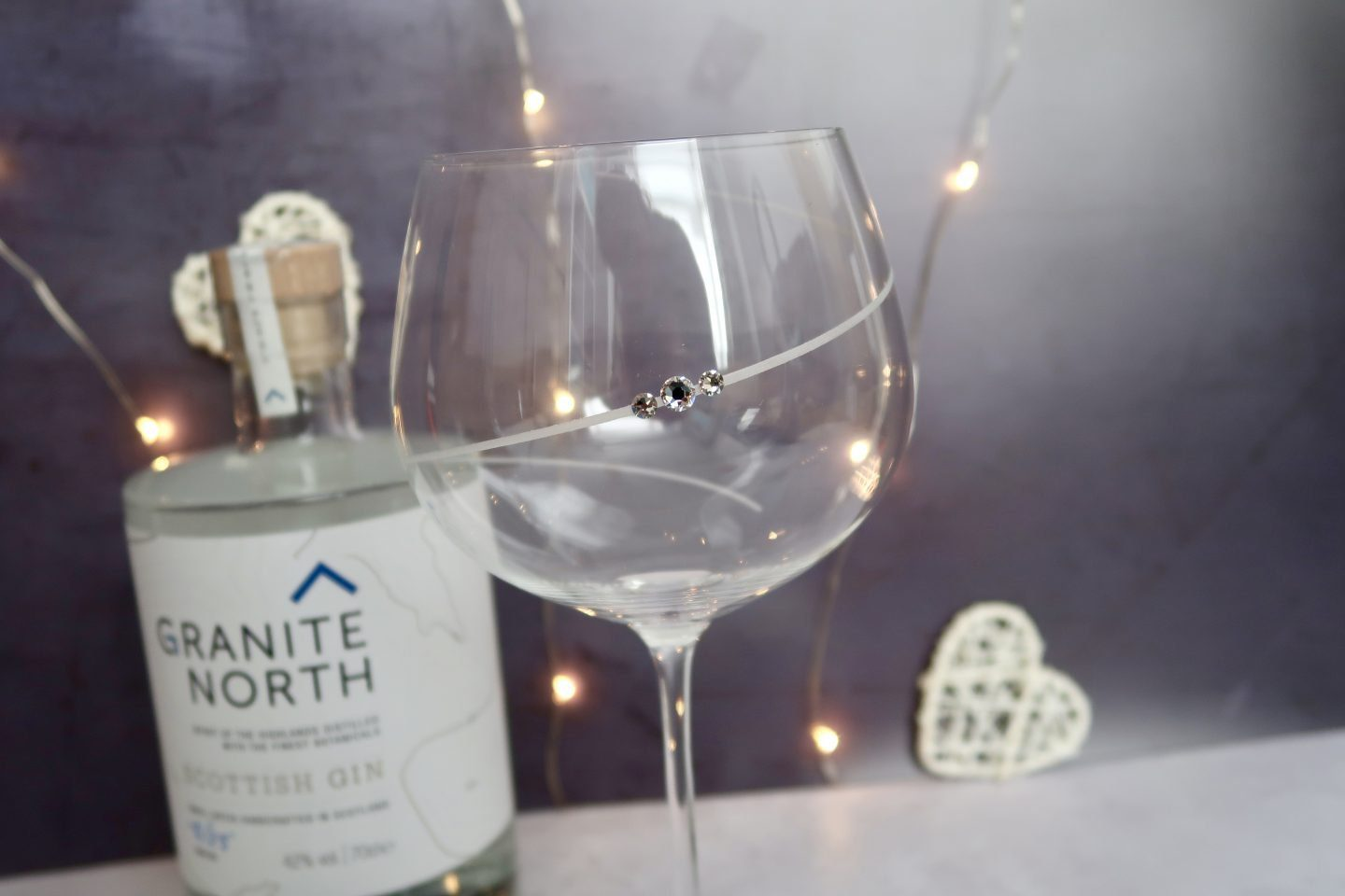 A gin glass with a crystal on it, in front of a bottle of gin and some fairy lights
