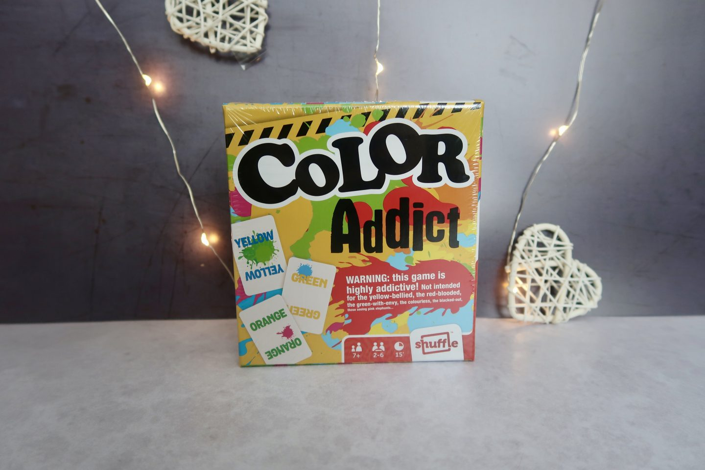 "A box with ""Color Addict"" written on it. The box sits infront of a grey background and fairy lights"
