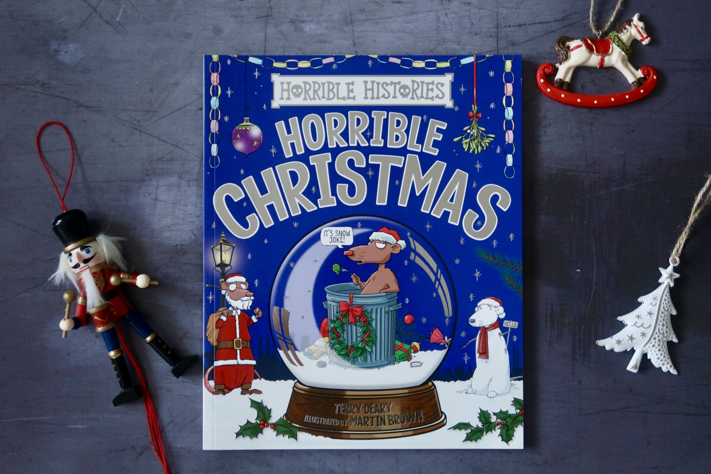 A blue book with Horrible Christmas written on it, along with a picture of a reindeer in a snow globe, a cartoon snowman and santa. Around the book are Christmas decorations