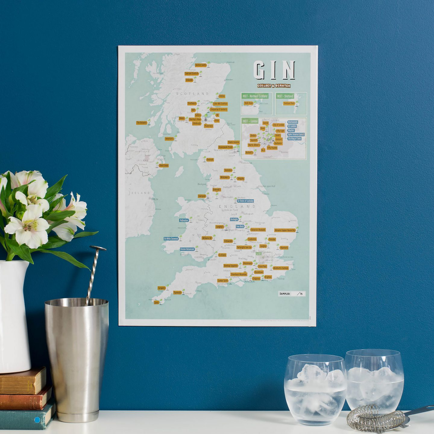 A map of the UK on a poster, with gin distilleries marked on it. The map is against a blue wall with some flowers next to them, and 2 glasses of gin and tonic with ice