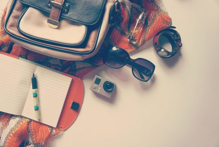 A bag with sunglasses, an open notebook and a go pro camera