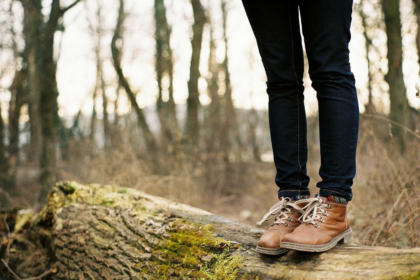The legs of a person wearing jeans and walking boots, standing on a log in the woods