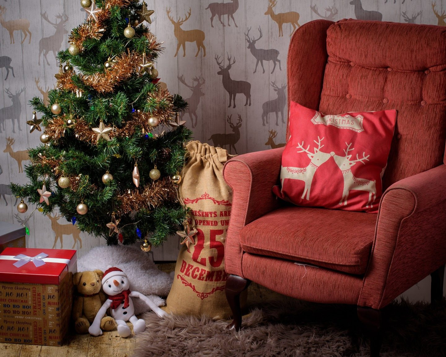 A Christmas tree with a santa sack and a red arm chair next to it