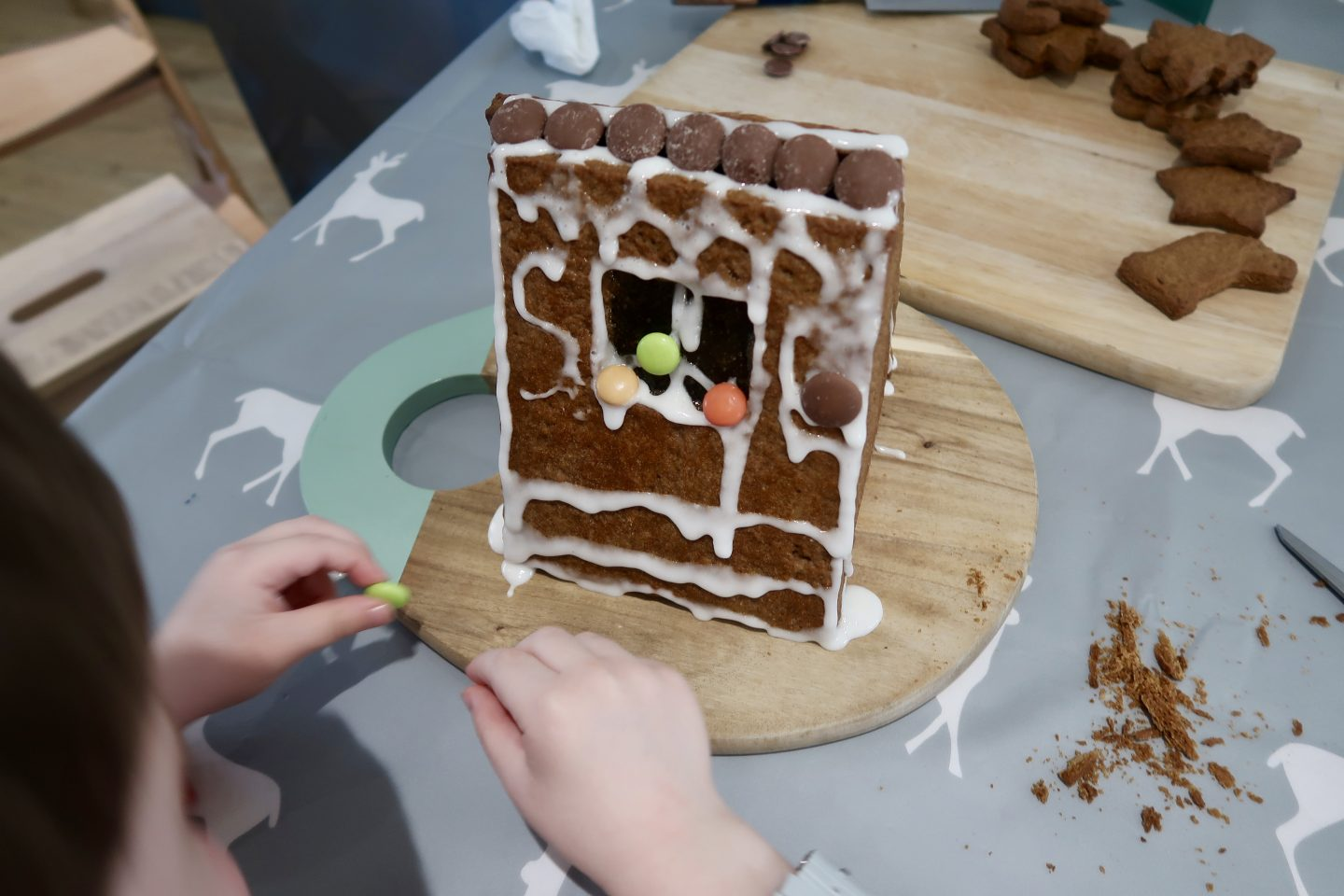 A gingerbread house being decorated by a toddler. On a wooden board behind it lies a pile of Christmas cookies