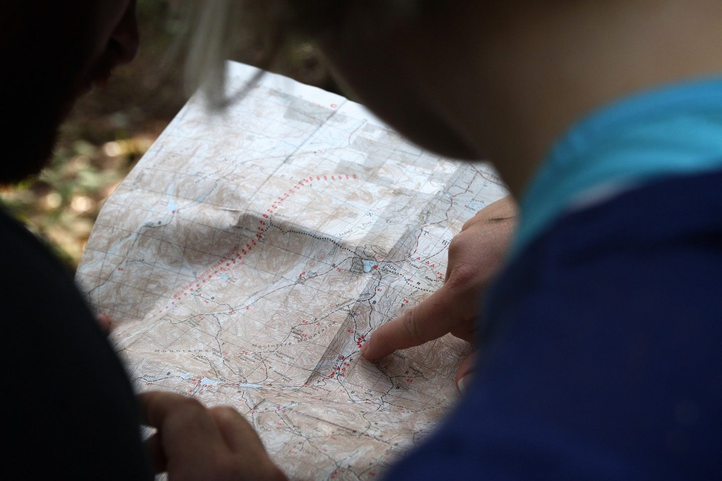 A paper map with 2 people looking at it, and one pointing at a spot with their finger
