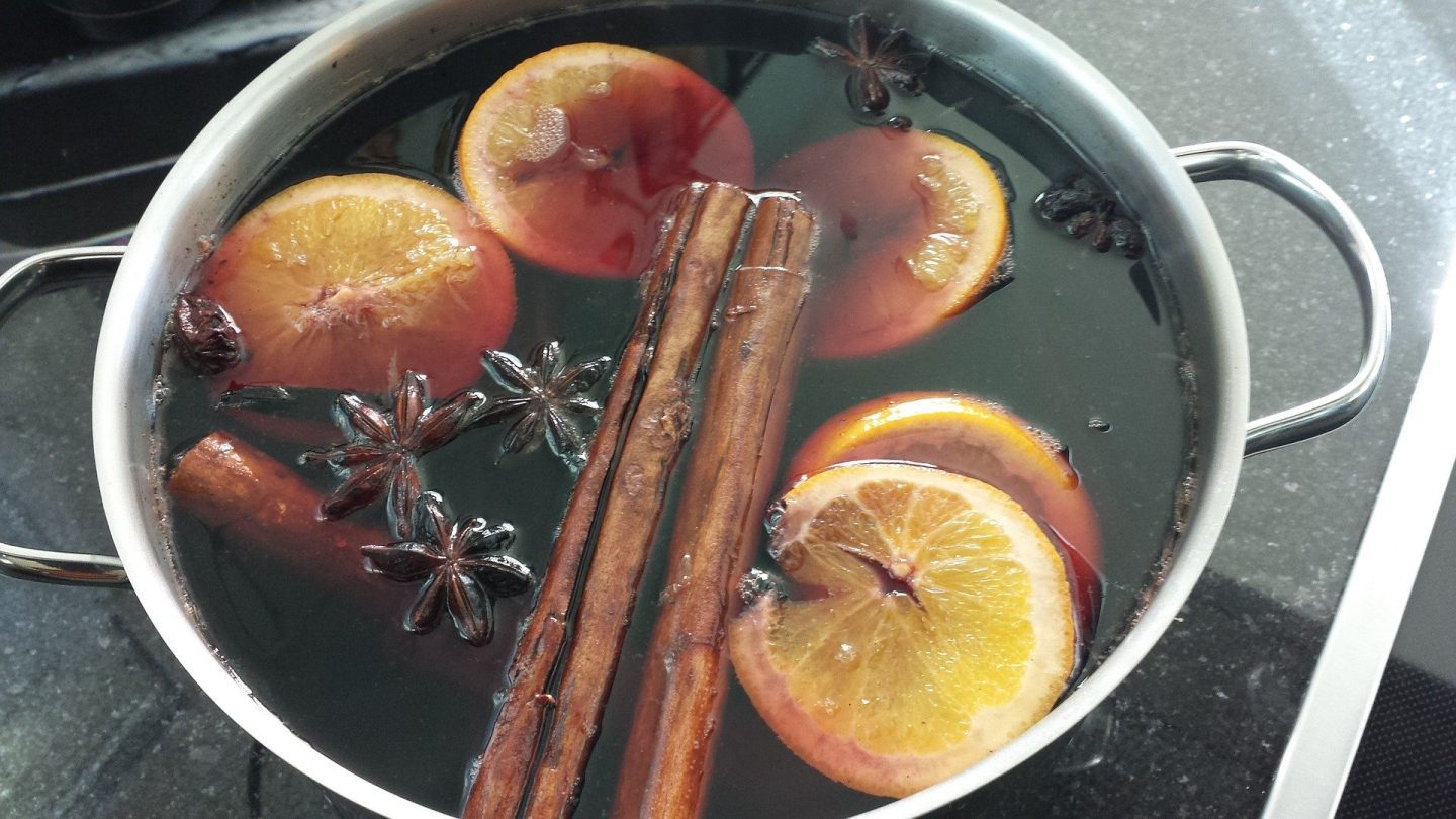 A large pot with the ingredients for mulled wine in it, red wine, oranges, cloves and cinnamon sticks