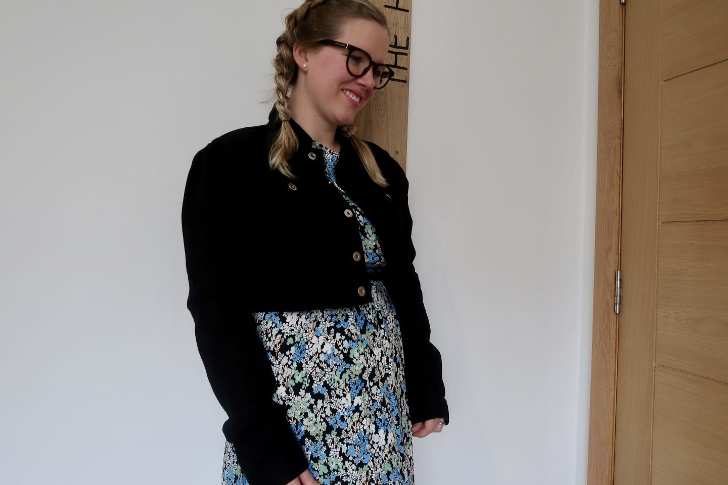 A woman wearing a floral print dress and a cropped black denim jacket