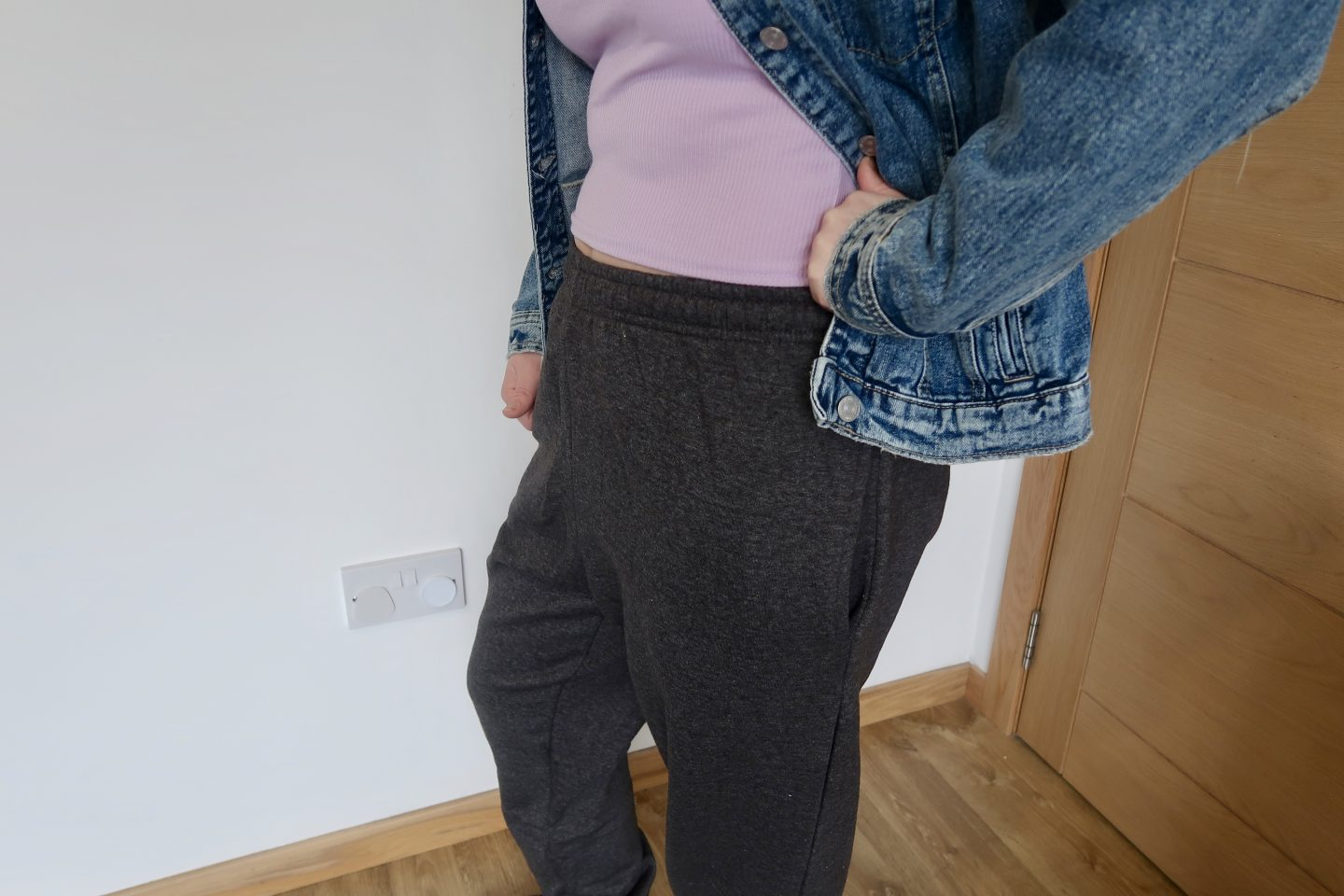 The torso of a woman in grey joggers, a lilac t-shirt and a denim jacket.  She has one hand on her hip, pulling the jacket to the side