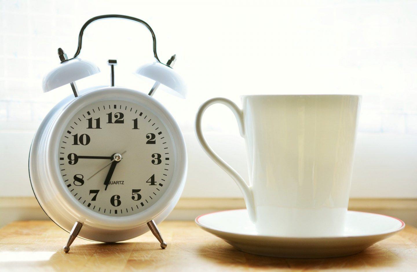A white alarm clock showing the time as 6:45, sitting next to a cup and saucer