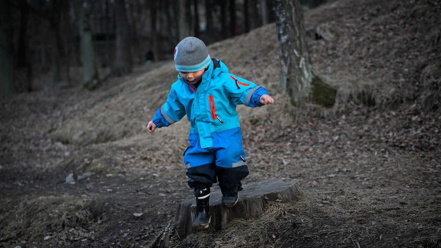 A child standing on a tree stump. He is dressed in blue waterproof and a hat and is looking down as if he is about to jump.