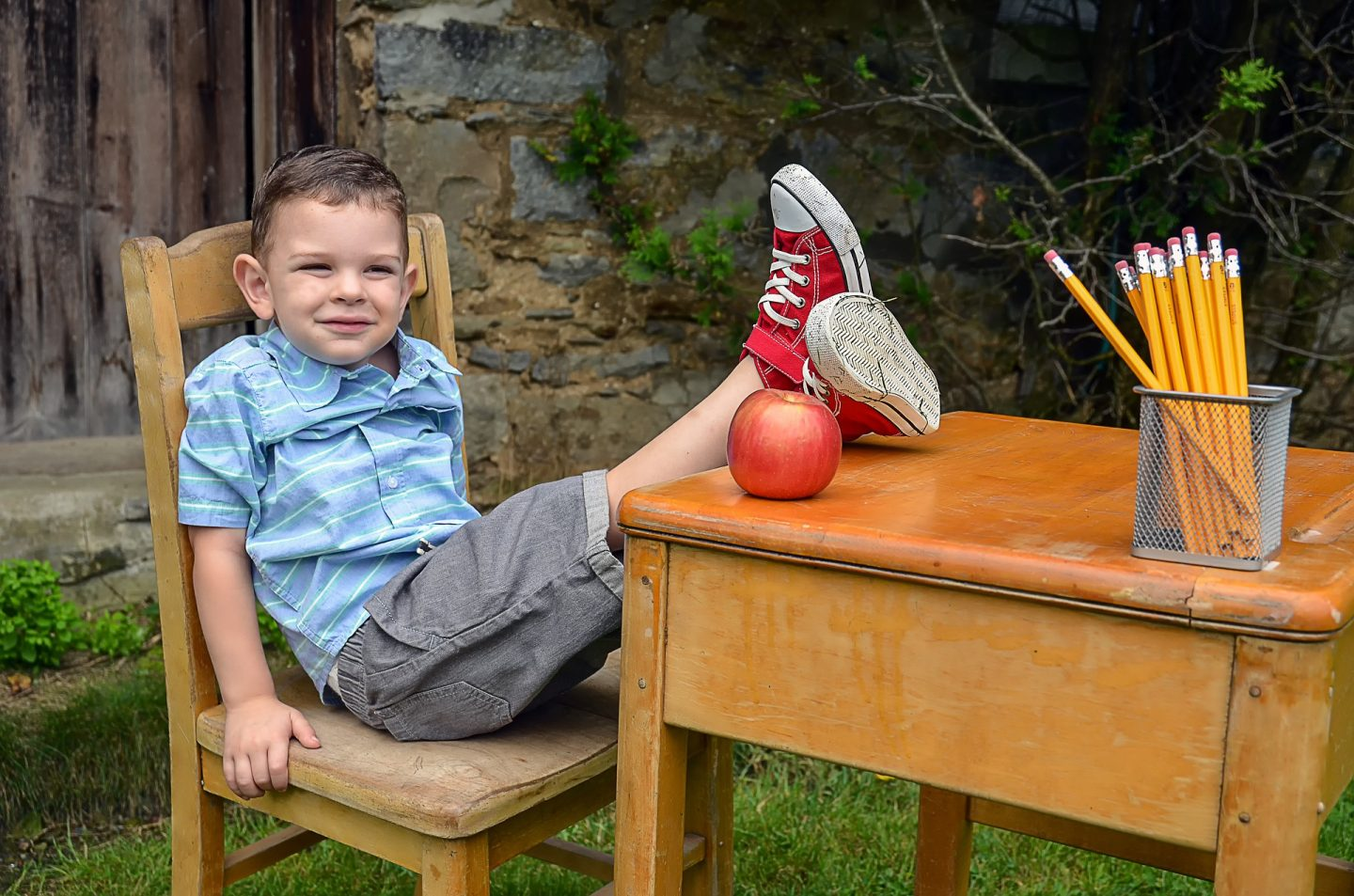 A little boy sits on a wooden chair with his feet up on a wooden desk. There is an apple and a dish of yellow pencils on the desk.