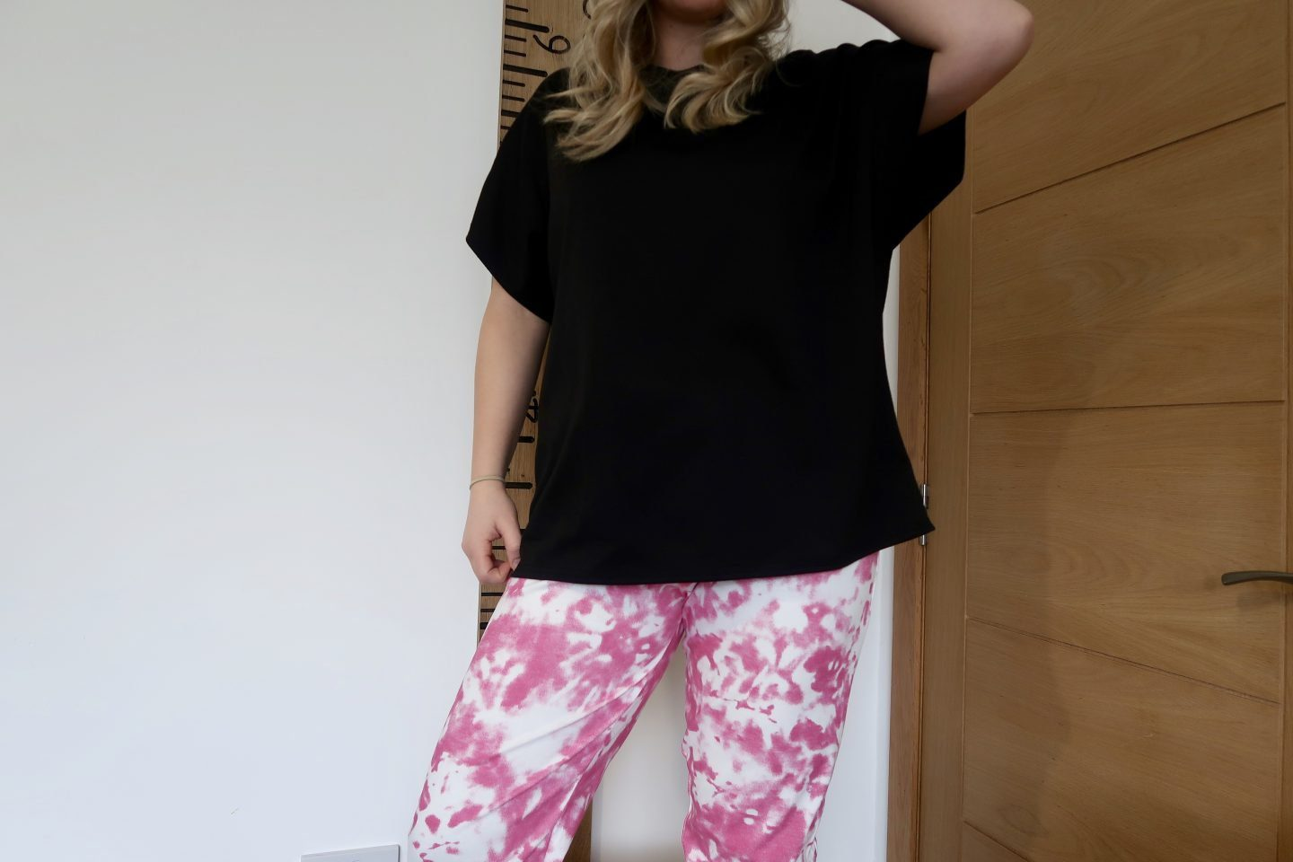 The torso of a woman wearing a black t-shirt and pink and white tie-dye joggers