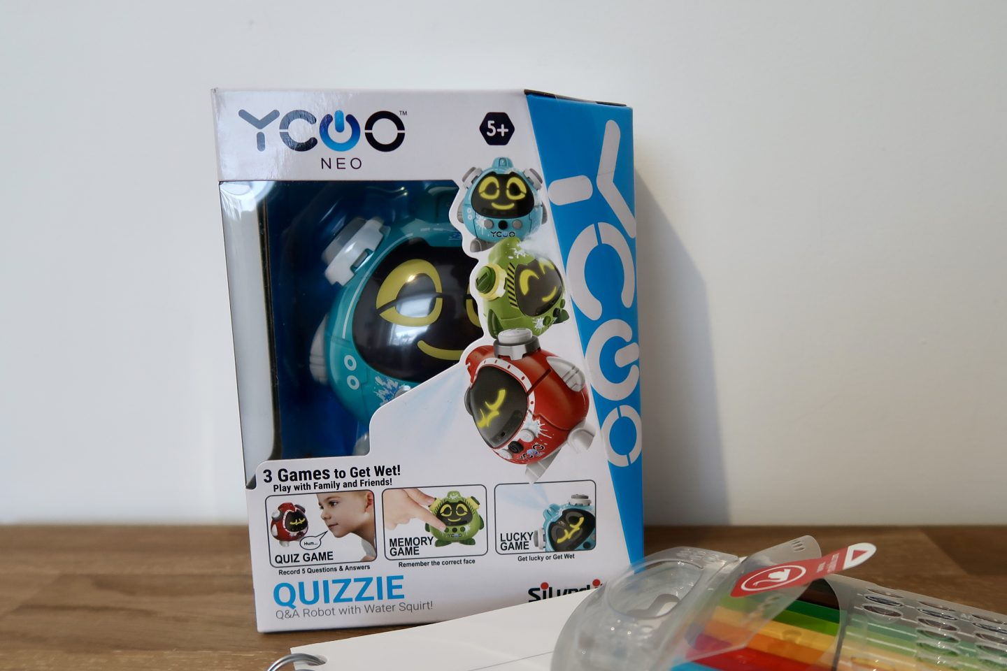 A Quizzie children's toy in it's box on a table with a notebook and pens