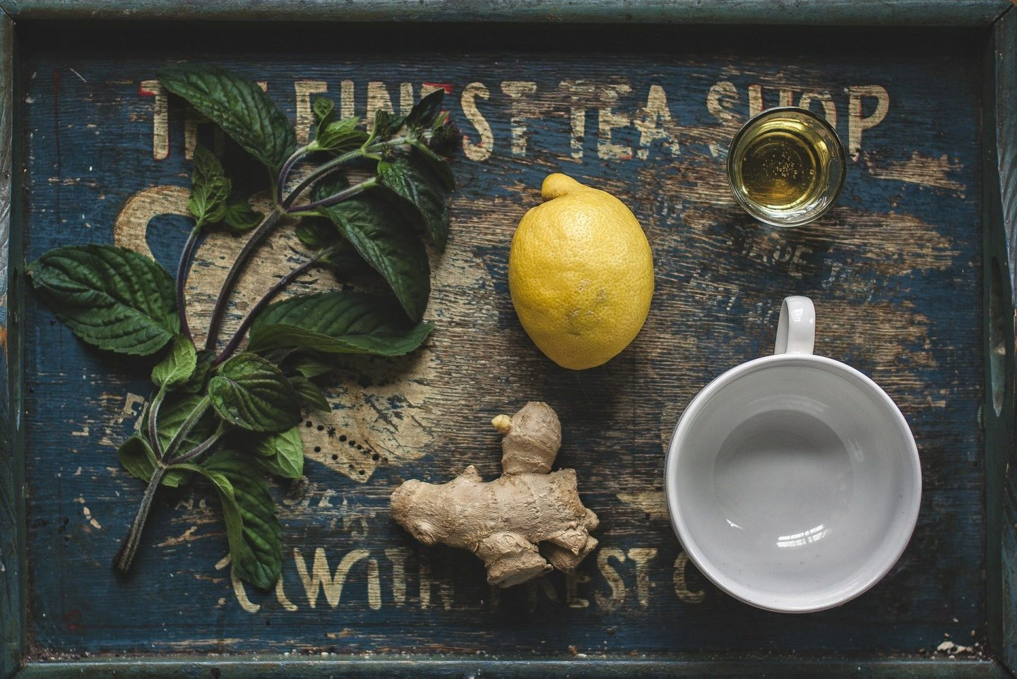 A dark blue tray with a white tea cup, lemon, ginger and mint on it