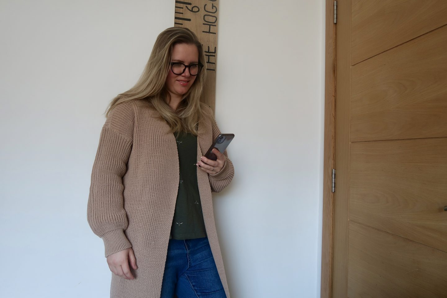 A woman leaning against a wall looking at her phone. She is wearing a tan coloured knitted cardigan and jeans.