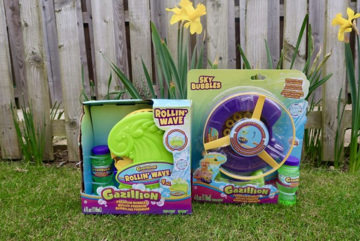 A Gazillion Bubble Rollin' Wave machine and a Sky Bubbles machine in their packaging ont he grass next to a daffodil