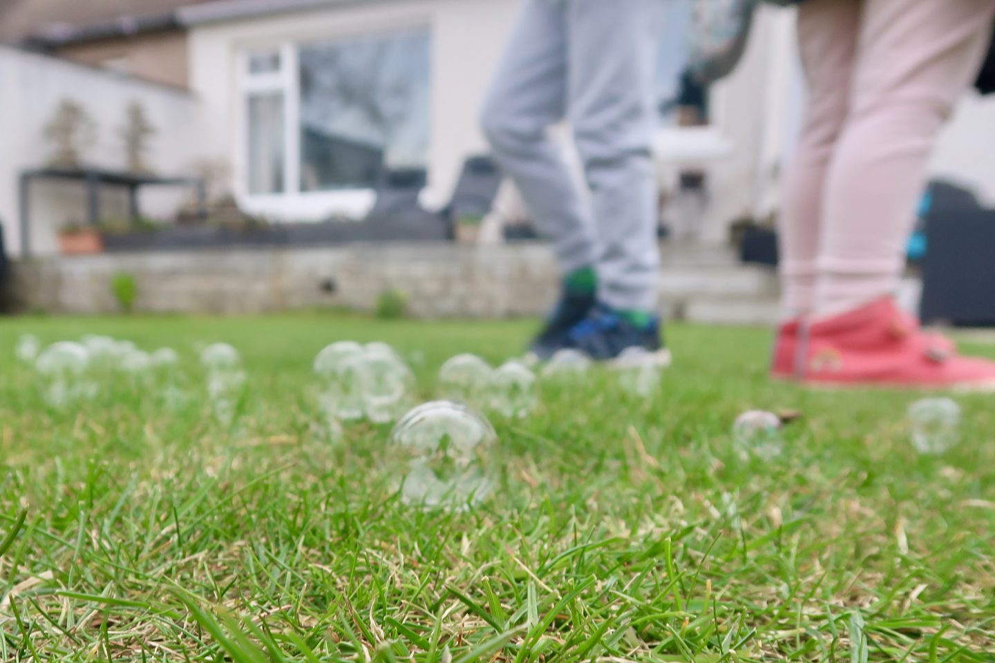 The legs and feet of some children, standing on grass that is covered in bubbles
