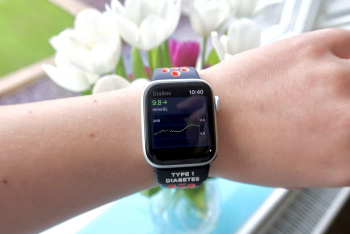 A smart watch on someones wrist, showing blood glucose readings from the Libre 2 via Diabox