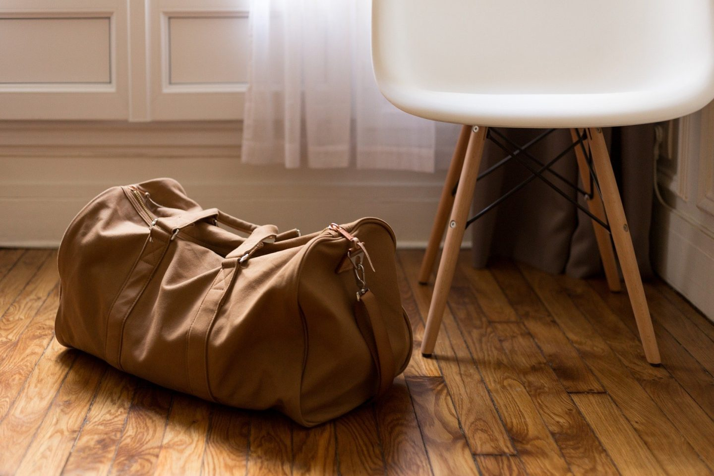 A brown holdall bag on a wooden floor next to a white chair
