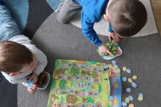 2 young boys playing a dinosaur board game