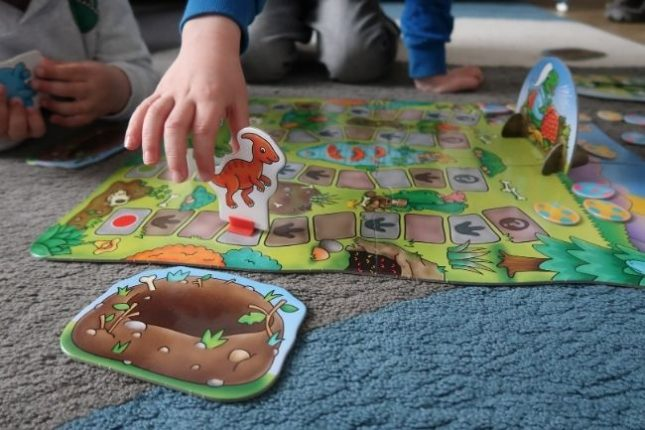 The Dino-Snore-Us game from Orchard Toys set up for play. A child's hand is holding one of the pieces