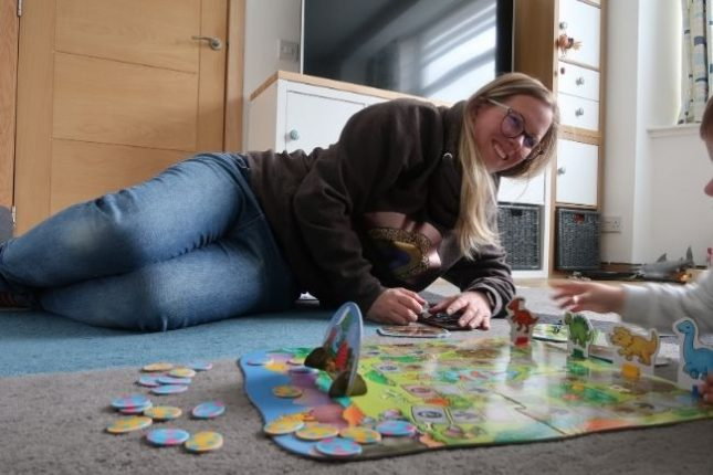 A woman playing a dinosaur board game on the floor