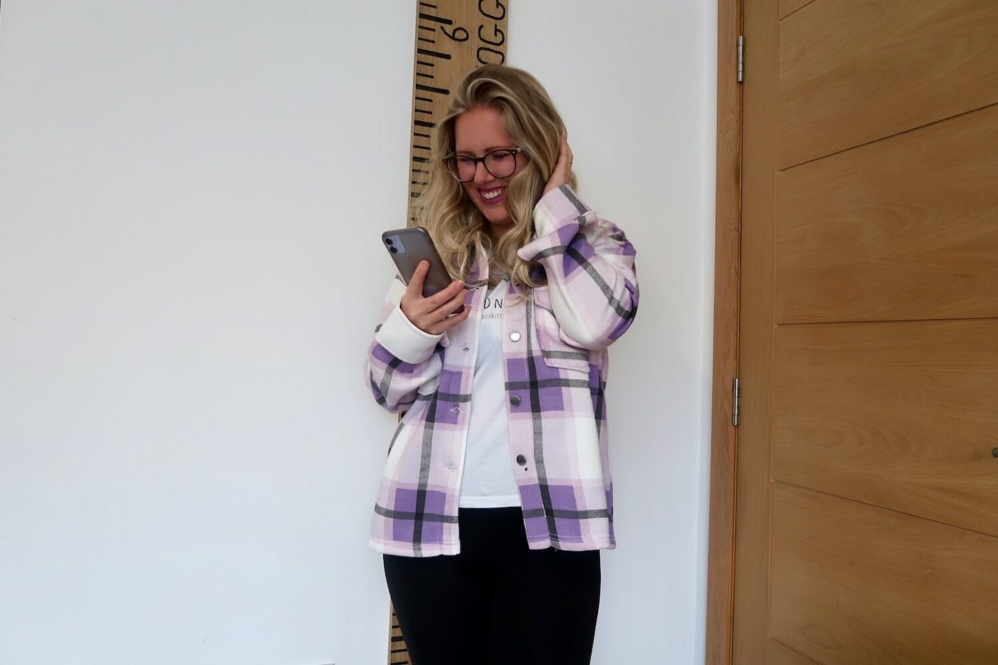 A woman with blonde hair is looking down at her phone and smiling. She is wearing a white and lilac checked shacket and black trousers, with one hand up and touching her her.