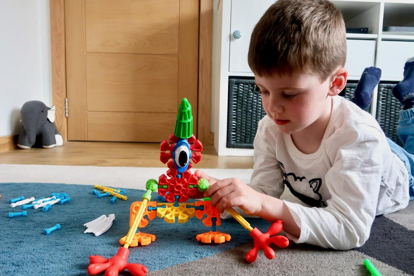A young boy holding the leg of a K'Nex creature he has made