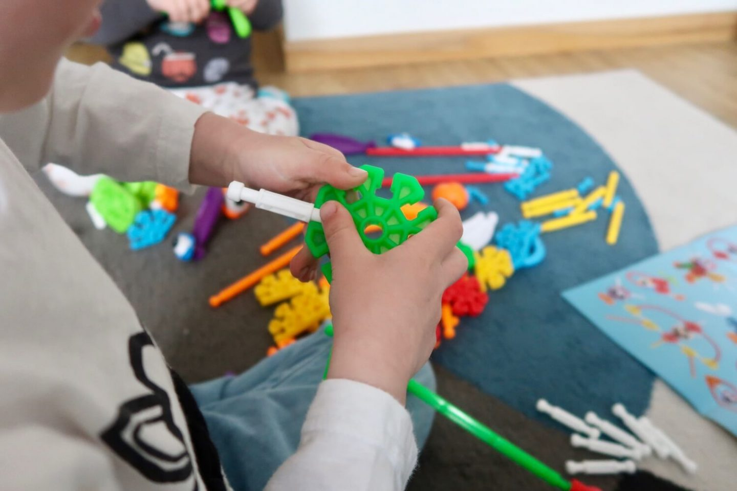 A child's hands holding some green Kid K'Nex connectors