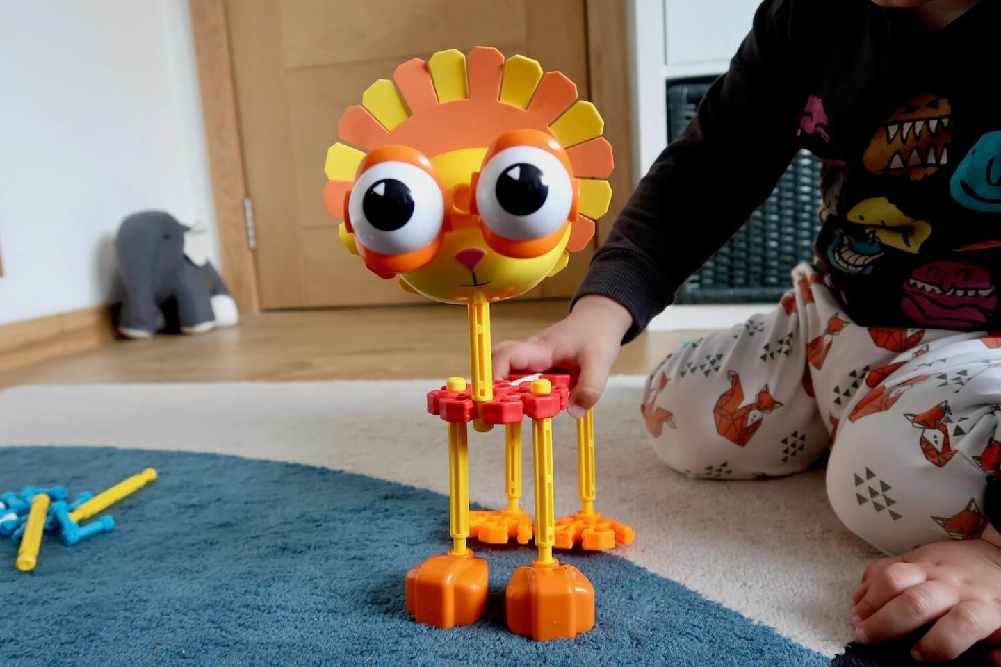 A lion made out of K'Nex with a child's hand on it's back