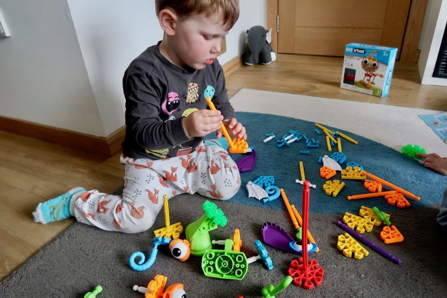A child sitting on the floor surrounded by Kid K'Nex pieces