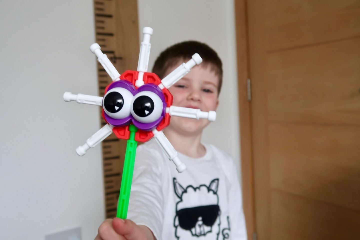 A child holding out a K'Nex monster