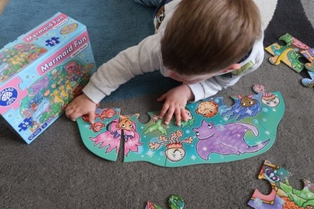 A boy lying on the floor doing a Mermaid Fun jigsaw puzzle from Orchard Toys
