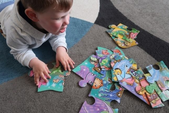 A boy lying on the floor, surrounded by jigsaw pieces