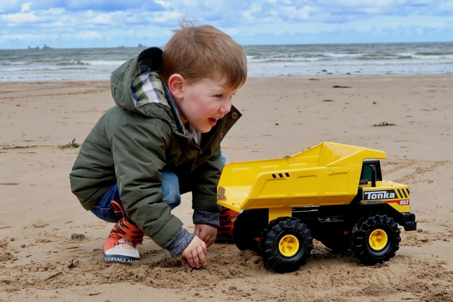 A child crouching next to a yellow toy dump truck on the beach.